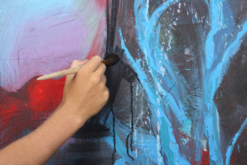 man hand painting blue abstract picture