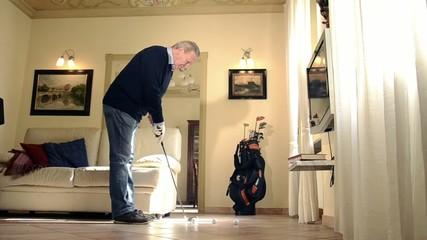 senior man practicing golf in living room