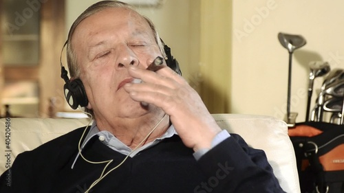 senior man smoking cigar and listening to music