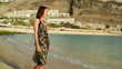 Woman standing by the sea, slow motion, steadicam shot