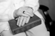 the elderly woman's hands on the book