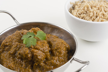 Goan Chicken Chacuti served & pilau rice on a white background