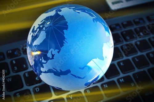 Blau beleuchteter Glasglobus auf Tastatur