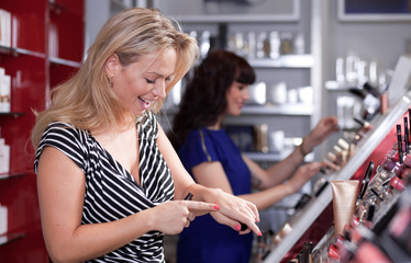 Women having fun while buying and testing cosmetics in a beauty