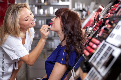Make up artist applying lipstick to a customer in a beauty store