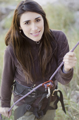 Young woman ready to rappel down a mountain