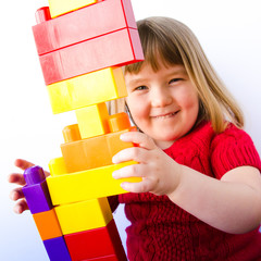 Close up of happy little girl building a tower