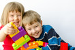 Two happy children play with blocks