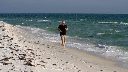 Mature Man Jogging Up Beach