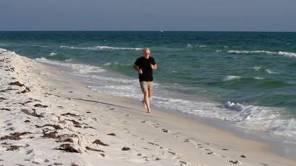 Mature Man Jogging Up Beach