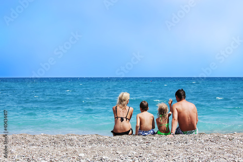 Family sitting back on beach