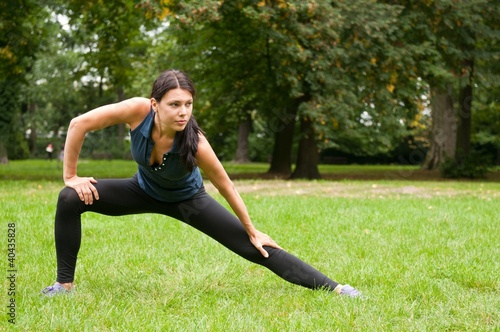 Woman performs stretching before sport in park