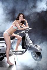 Junge hübsche Frau sitzt in Dessous auf Roller