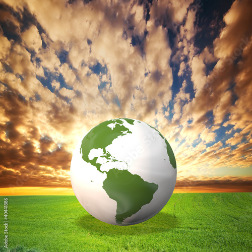 Planet Earth model on green field at sunset
