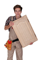 Young carpenter holding cupboard door