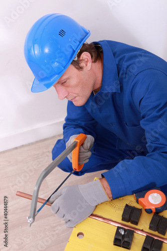 Man sawing copper pipe