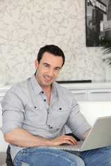 smiling man with laptop indoors