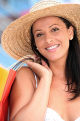 Woman in straw hat holding shopping bags