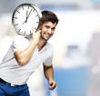 portrait of a handsome young man carrying a clock against a abst