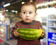 portrait of sweet kid holding a big watermelon against a shop