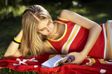 young lady in the garden reading and relaxing on the red towel