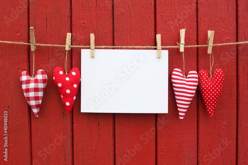 Herzen mit Zettel hinter rotem Holz