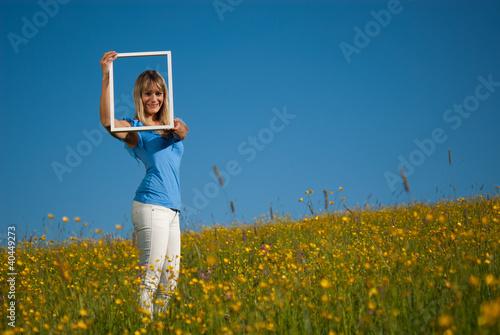junge Frau mit Bilderrahmen in der Natur