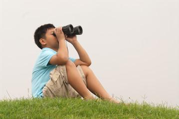 Boy looks into binoculars on top of hill .