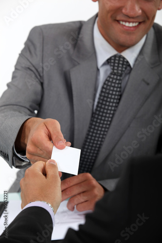 Businessman handing his card to a potential client