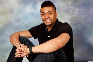 Handsome black man sitting on floor smiling