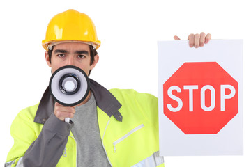 road worker holding a stop sign and talking through a megaphone