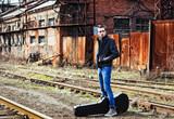 Young man with guitar case waiting for train among industrial ru