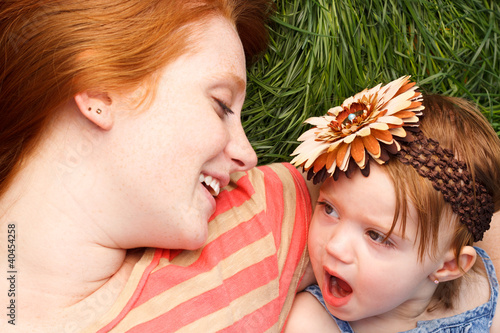 Smiling Mother And Daughter Laying In Tall Grass