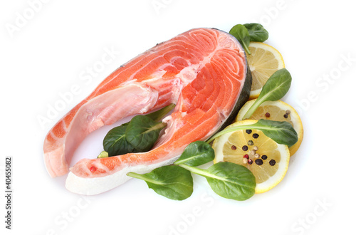 Red fish with lemon, green leaves and pepper isolated on white.