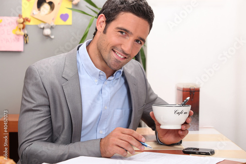 Businessman working in his kitchen with a cup of coffee
