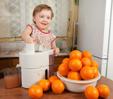 Baby girl making fresh orange juice