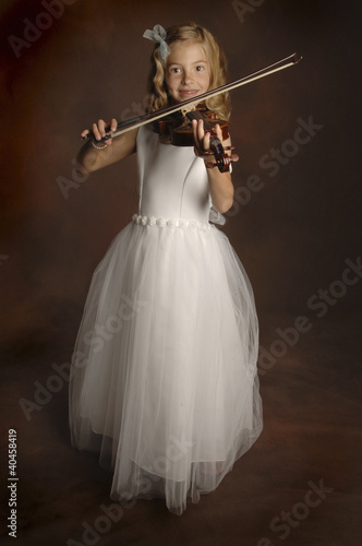 A girl in white lacy dress playing violin.