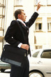 Side shot of a man in business suit with a sling bag stopping a taxi.