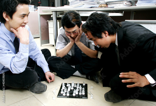 A group of men playing chess in the office.