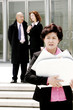 An angry looking woman holding a briefcase of papers.