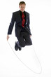 Man in business suit playing with skipping rope.