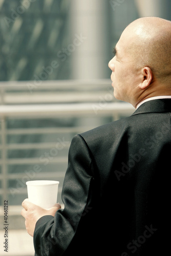 Back shot of a bald man in business suit holding a cup.