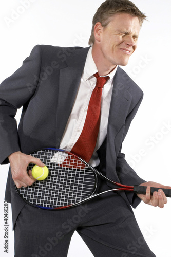 Businessman holding a tennis racquet and ball like playing a guitar.