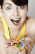Woman with handful and mouthful of candies.