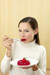 Woman eating strawberry jelly.
