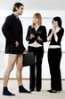 Businesswomen laughing at their colleague for not wearing pants to work.