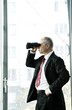 Businessman using binoculars.