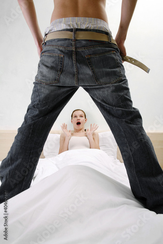Man taking off his pants shocking his wife.