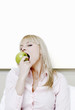 Businesswoman biting a green apple.