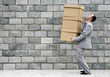 Businessman carrying a stack of boxes.